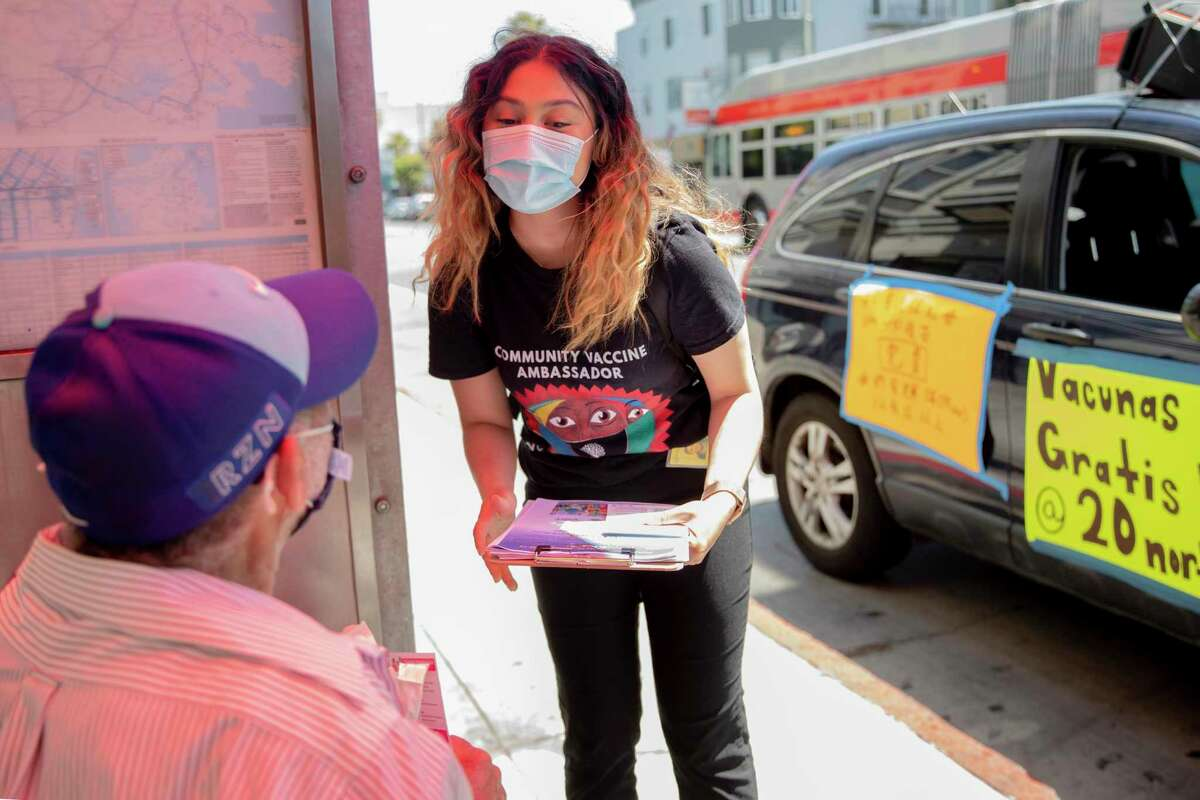 Kathrine Flores discusses vaccinations last month during a visit to a bus stop on Mission Street in San Francisco.