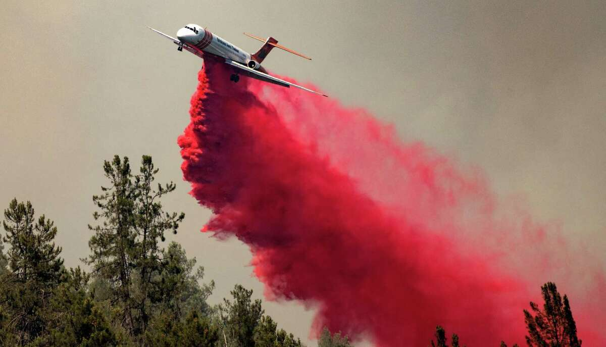 An air tanker drops retardant along a ridge during the Salt Fire in Lakehead (Shasta County).