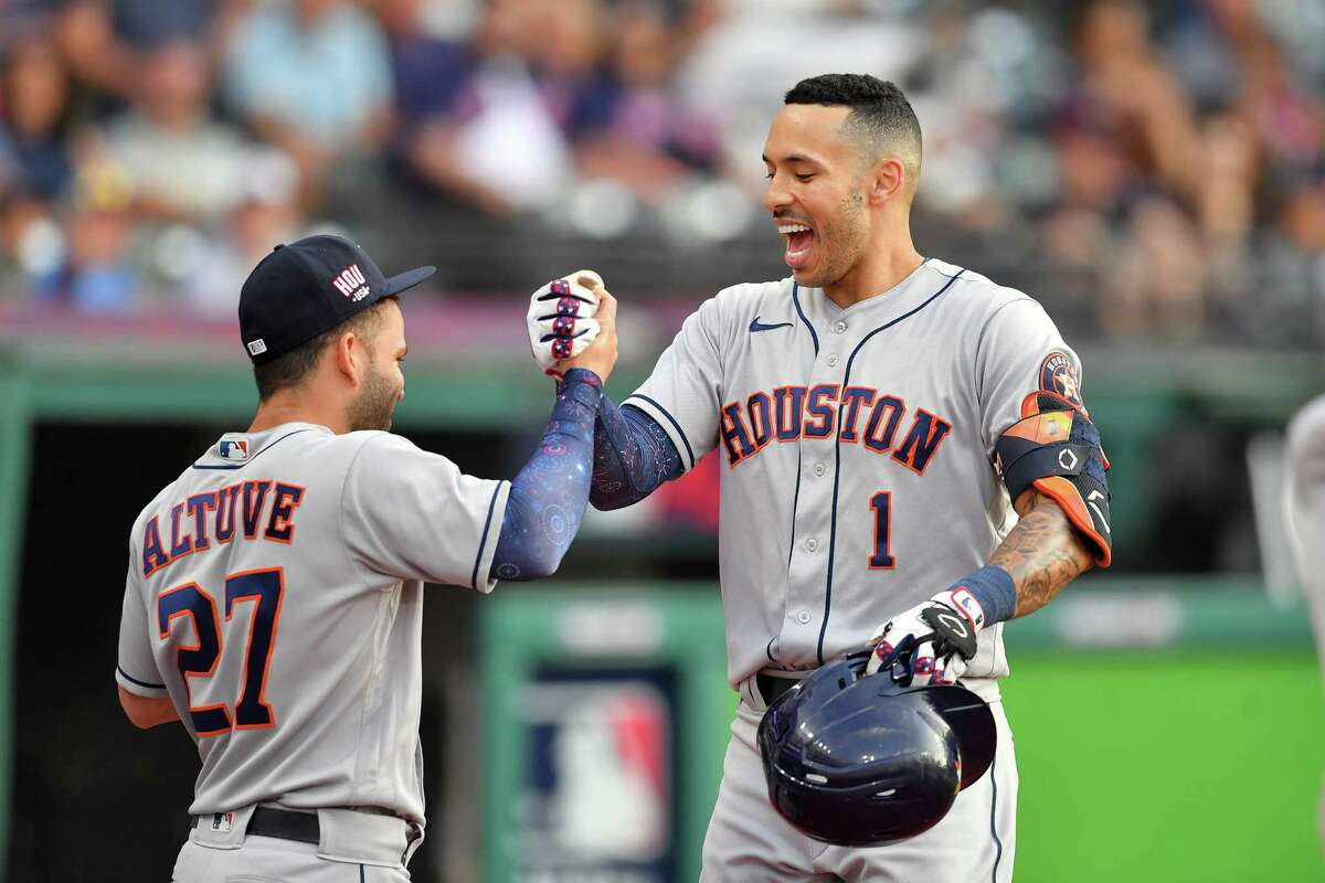 Jose Altuve #27 celebrates with Carlos Correa #1 of the Houston Astros after Correa hit a solo homer during the fourth inning against the Cleveland Indians at Progressive Field on July 03, 2021 in Cleveland, Ohio.