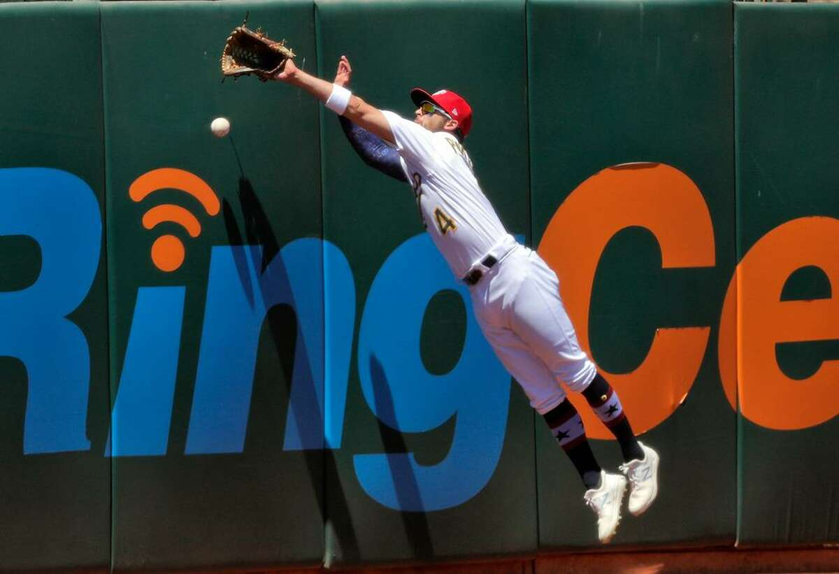 Chad PInder (4) leaps against the wall but cant get to a ball hit by. Alex Verdugo (99) in the sixth inning as the Oakland Athletics played the Boston Red Sox at the Coliseum in Oakland, Calif., on Sunday, July 4, 2021.