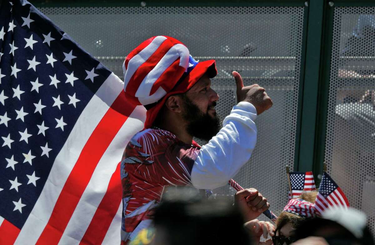 A star-spangled fan walks around the coliseum waving a flag in his flag attire as the Oakland Athletics played the Boston Red Sox at the Coliseum in Oakland, Calif., on Sunday, July 4, 2021.