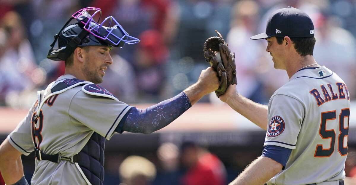 Houston Astros relief pitcher Brooks Raley, right, is congratulated by catcher Jason Castro after the Astros defeated the Cleveland Indians 4-3 i ten innings in a baseball game, Sunday, July 4, 2021, in Cleveland. (AP Photo/Tony Dejak)