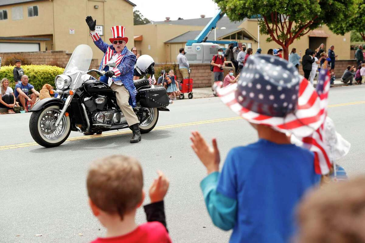 Outfitted as Uncle Sam, Harry Ysselstein waves at spectators during the Half Moon Bay Ol' Fashioned 4th of July Parade on Main Street.