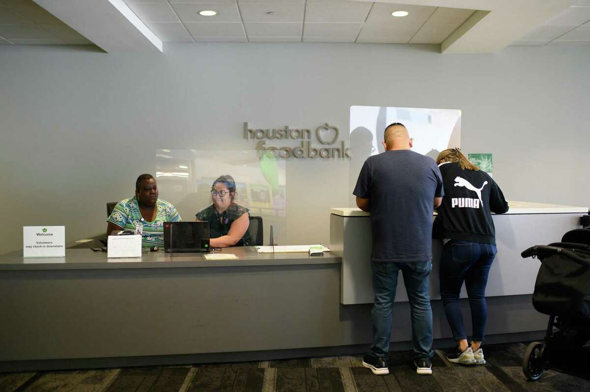 A young family starts the application process at the Benefit center at the Houston Food Bank on Friday, July 2, 2021