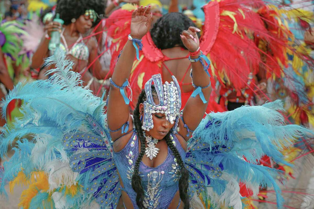 """A dancer is surrounded by others during the Houston Caribbean Festival celebration with a """"parade consisting of men and women in costume, stilt walkers, steel drums and floats Sunday, July 4, 2021, in Houston."""