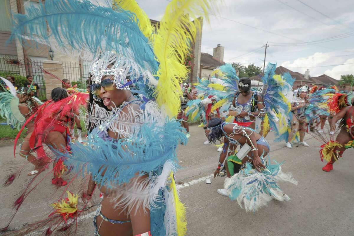 """Dancers perform during the Houston Caribbean Festival celebration with a """"parade consisting of men and women in costume, stilt walkers, steel drums and floats Sunday, July 4, 2021, in Houston."""
