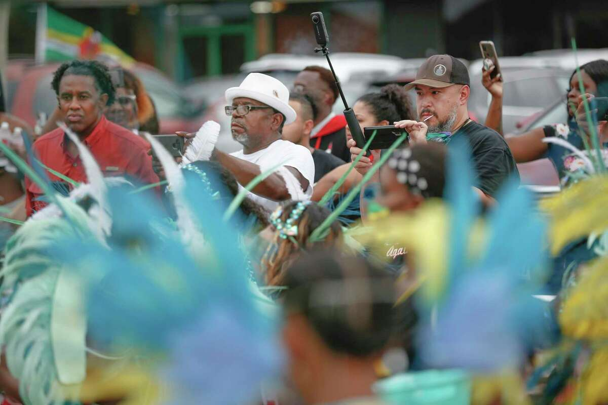 """Spectators take in the dancers during the Houston Caribbean Festival celebration with a """"parade consisting of men and women in costume, stilt walkers, steel drums and floats Sunday, July 4, 2021, in Houston."""
