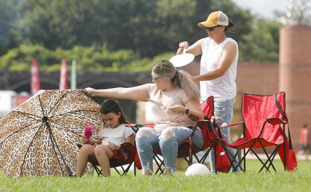 Gabby Carrillo, center, helps shade her daughter, Sophia, from the sun as GabbyÕs wife, Malenie Carrillo cools her down with a fan during The Woodlands Township's Red, Hot & Blue Festival at Town Green Park, Sunday, July 4, 2021, in The Woodlands. Photo: Jason Fochtman/Staff Photographer / ? 2021 Houston Chronicle