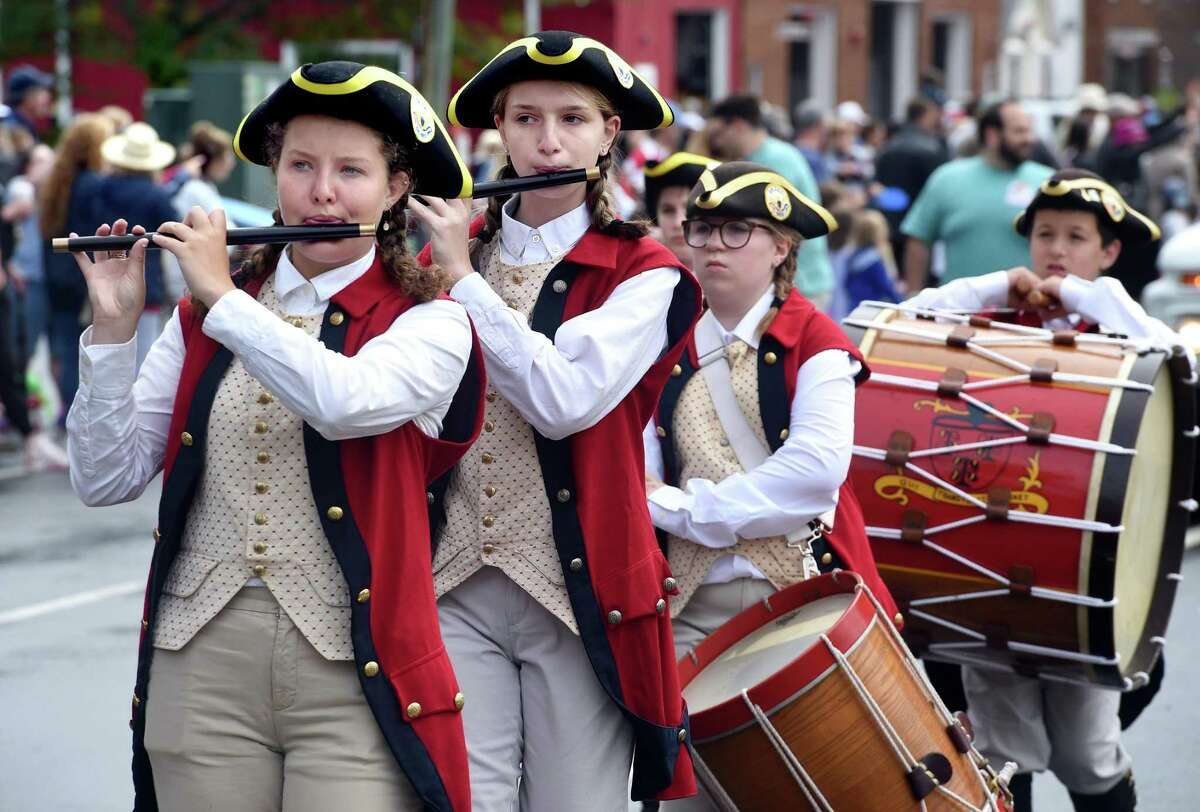 Members of the Deep River Junior Ancients Fife & Drum Corps march in an Independence Day Parade in Madison Sunday. At left,