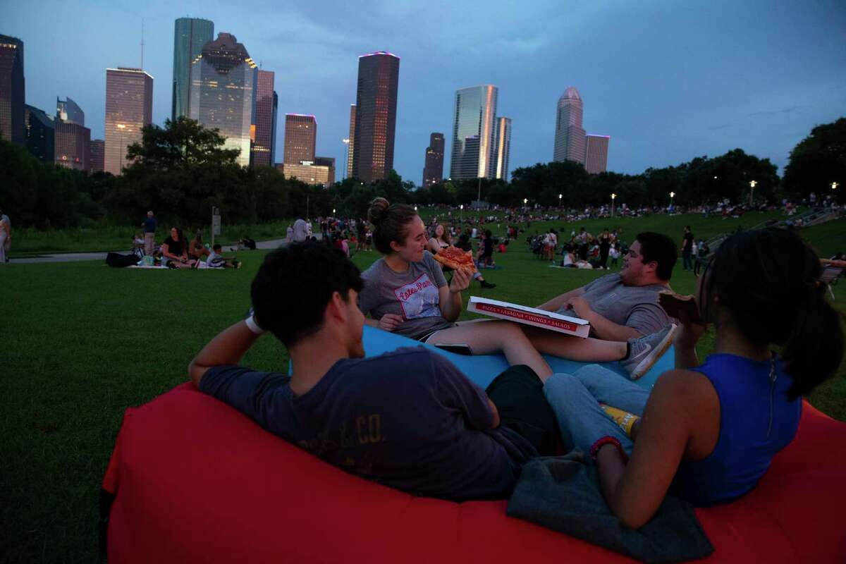 Natalie Confer, clockwise, Rodrigo Alvarado, Emilie Mascorro and Fernando Alvarado have pizza and wait for the 2021 Shell Freedom Over Texas fireworks show Sunday, July 4, 2021, from Eleanor Tinsley Park in Houston. While the concert is still virtual this year, people were allowed to be at the park to watch the fireworks.