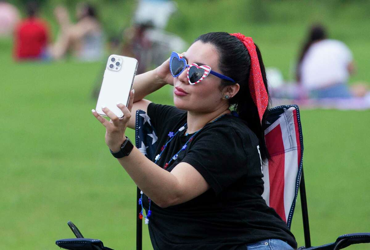 Marlene Ramirez takes a selfie while waiting for the 2021 Shell Freedom Over Texas fireworks show Sunday, July 4, 2021, from Eleanor Tinsley Park in Houston. While the concert is still virtual this year, people were allowed to be at the park to watch the fireworks.