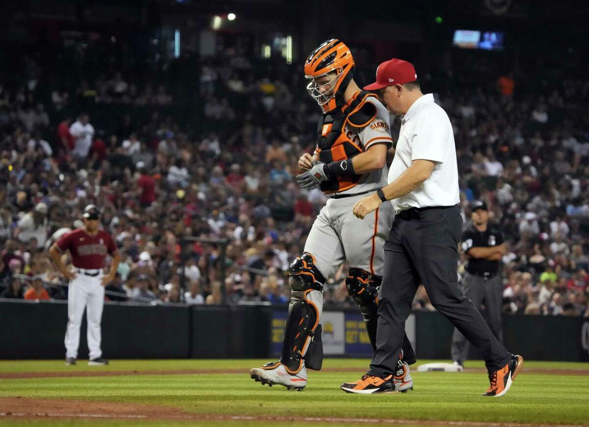 San Francisco Giants catcher Buster Posey leaves the game with a trainer after getting hit with the ball in the sixth inning of a baseball game against the Arizona Diamondbacks, Sunday, July 4, 2021, in Phoenix. (AP Photo/Rick Scuteri)