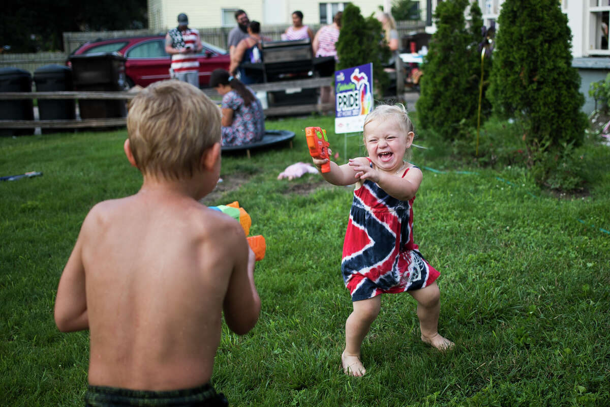 Aaliyah Quinones, 2, right, and Braydon Stewart, 6, left, play with water guns as thousands of people gather for a live concert and fireworks display Monday, July 4, 2021 at Dow Diamond in Midland. (Katy Kildee/kkildee@mdn.net)
