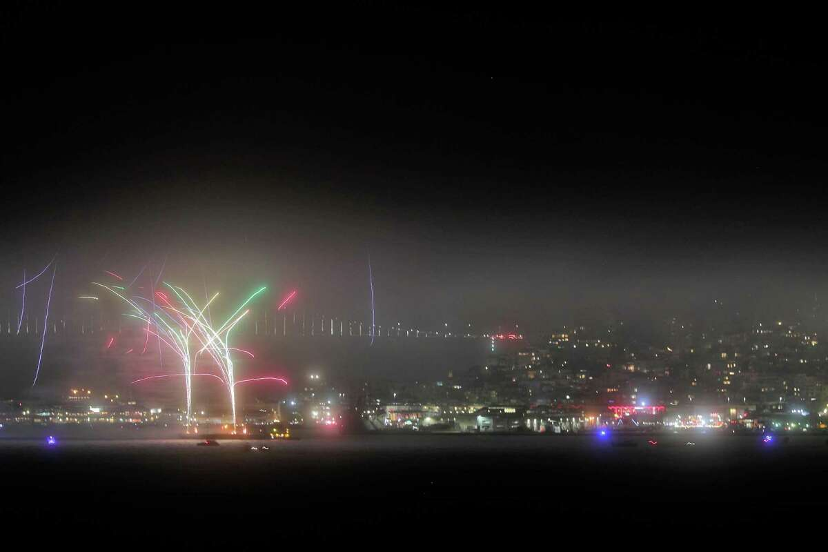 Fireworks light up over San Francisco Bay as seen from Sausalito through fog that prevented higher fireworks from being seen.