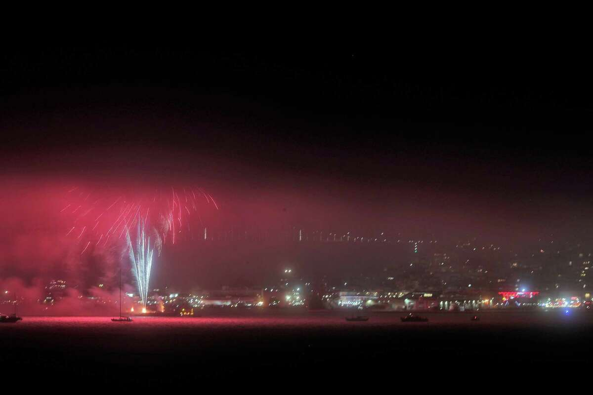 Fireworks over the bay off of San Francisco's waterfront light up the sky beneath high clouds and fog.