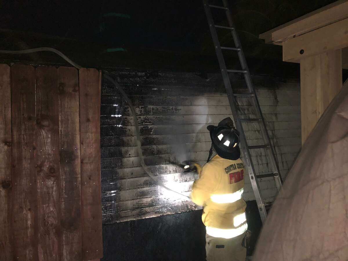 A Contra Costa County firefighter battles a blaze at a Pittsburg house caused by errant fireworks.