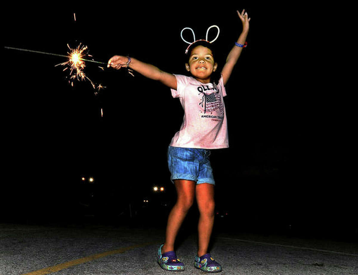 Bria Young, 6, of Glen Carbon dances as she plays with a sparkler at the Edwardsville Independence Day Celebration Saturday at American Legion Post 199.