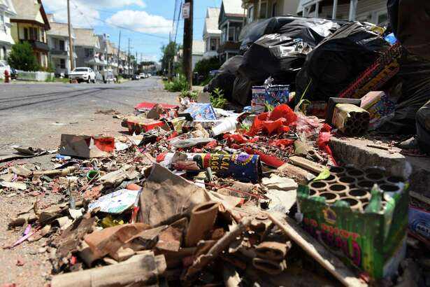 Debris from a neighborhood firework display is swept into a pile with other trash along Hulett Street on Monday, July 5, 2021, in Schenectady, N.Y. (Will Waldron/Times Union)