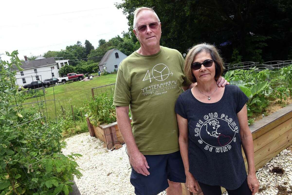 Bill Freeman and his wife, Alicia Dolce, are photographed in the front yard of their home in Guilford next to the property (left) of Eunice Demond of Little Rascals Rescue and Rehabilitation on July 1, 2021, where Demond is seeking a special use permit for her animal rescue operation.