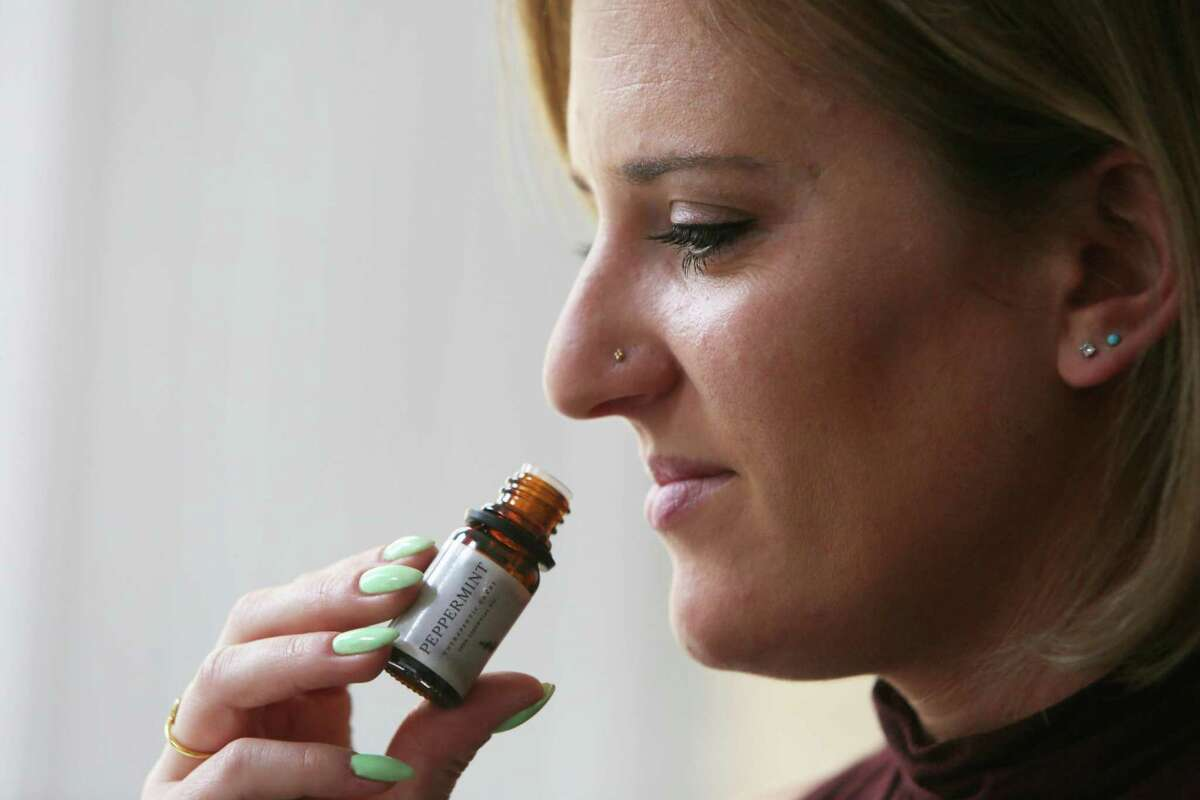 Cat Berner of San Francisco, who lost her sense of smell when she got COVID-19 in October, smells an essential oil while conducting scent training.