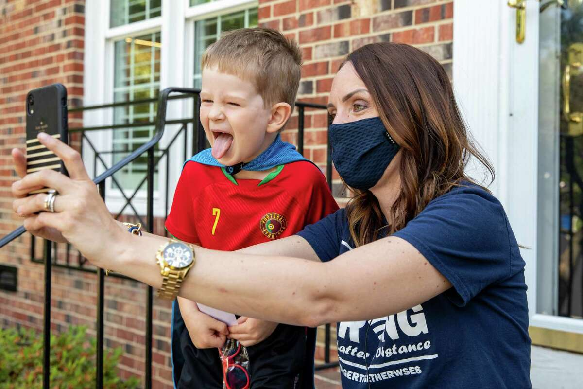 Henry Ellison, 5, poses for a selfie with his principal at West Springfield Elementary School, Kelly Sheers, as she conducts home visits in June in Fairfax County, Va.