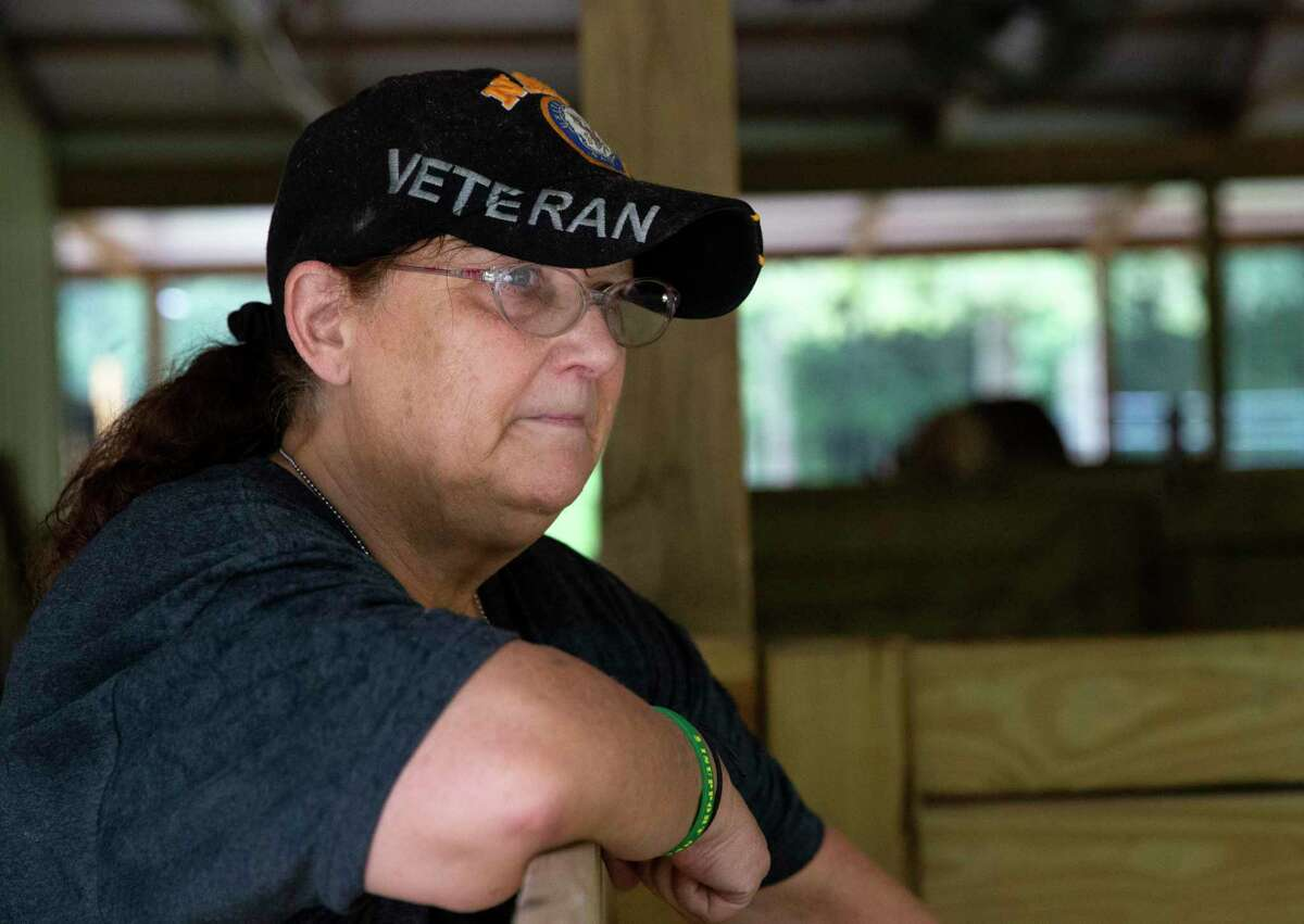 """Romana Harding, a U.S. Navy veteran and sex assault survivor, hangs on the stall and watches her miniature horses on her livestock farm Saturday, July 3, 2021, at Pine Shadows Farm in Cleveland. Harding, who has PTSD, said her farm is her recharging place to get away from her stress and pain. She called working with animals her therapy. """"It's like they know,"""" Harding said."""