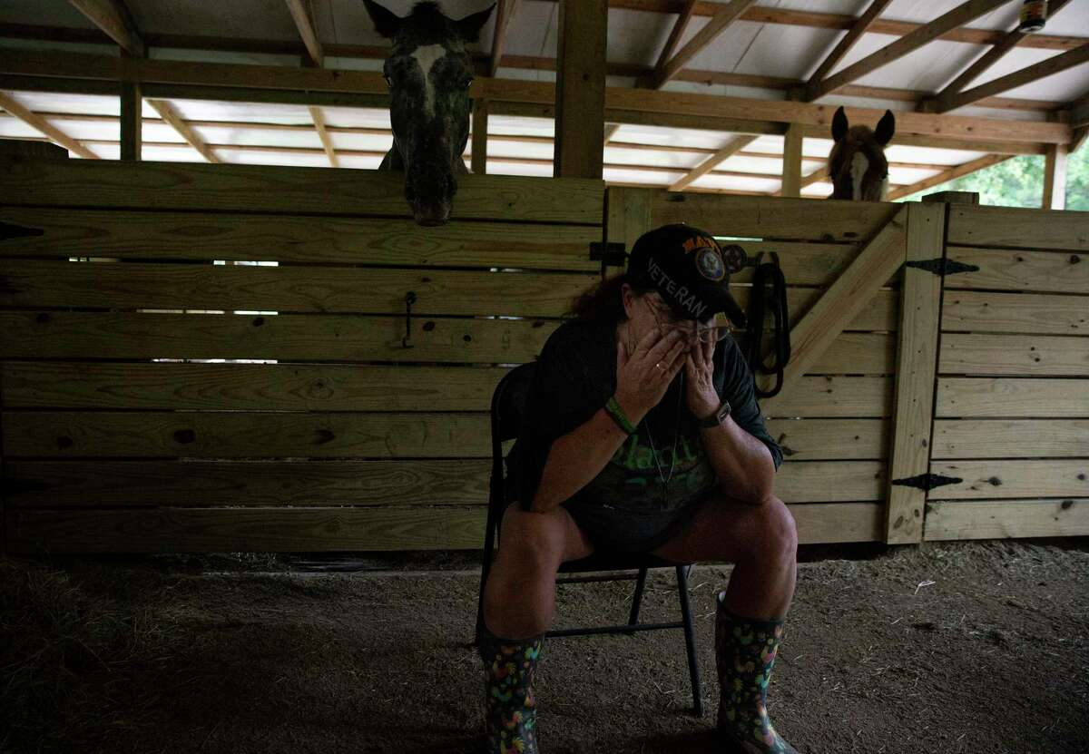 """Romana Harding, a U.S. Navy veteran and sex assault survivor, has to sit down at her barn as she experiences a moment of dissociation on her livestock farm Saturday, July 3, 2021, at Pine Shadows Farm in Cleveland. Harding, who has PTSD, said her farm is her recharging place to get away from her stress and pain. She called working with animals her therapy. """"It's like they know,"""" Harding said."""