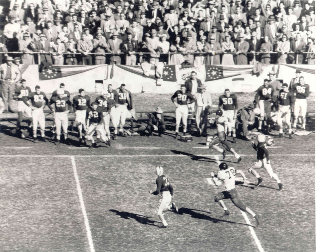 Dick Maegle of Rice runs with the ball down the sideline in the 1954 Cotton Bowl against Alabama. At left, Alabama's Tommy Lewis (42) is seen taking steps toward the field. courtesy of the Cotton Bowl,