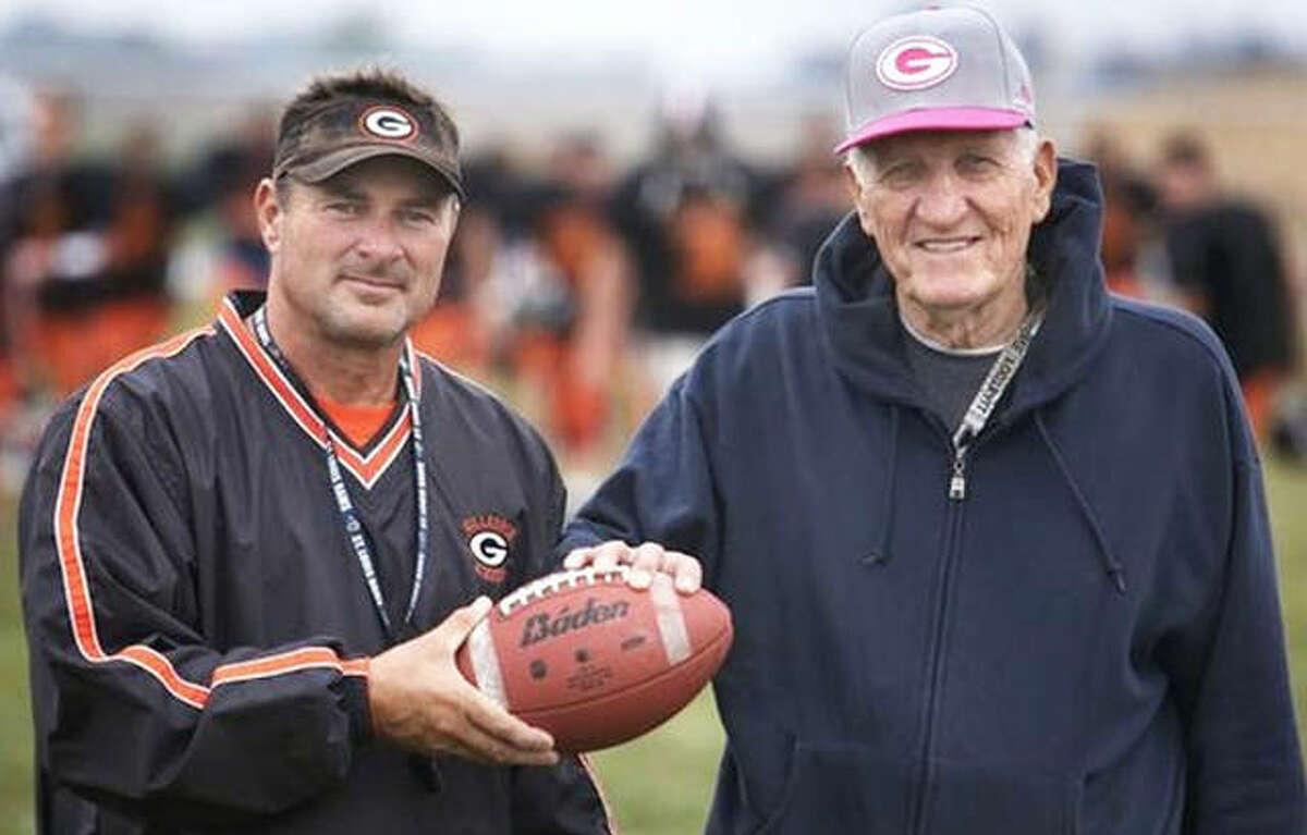 Gillespie coach Don Dobrino (right) and Don Borgini pose with a ball that first began their bond in 1973 when Borgini was a freshman quarterback and Dobrino was the Miners football coach. Dobrino died Sunday at 86.