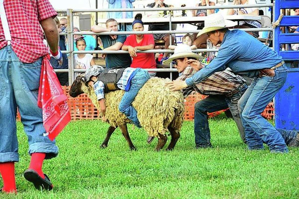 A young cowboy holds on tightly during the mutton-busting contest during the Franklin Fourth of July Celebration. (More photos from the celebration available at myjournalcourier.com)