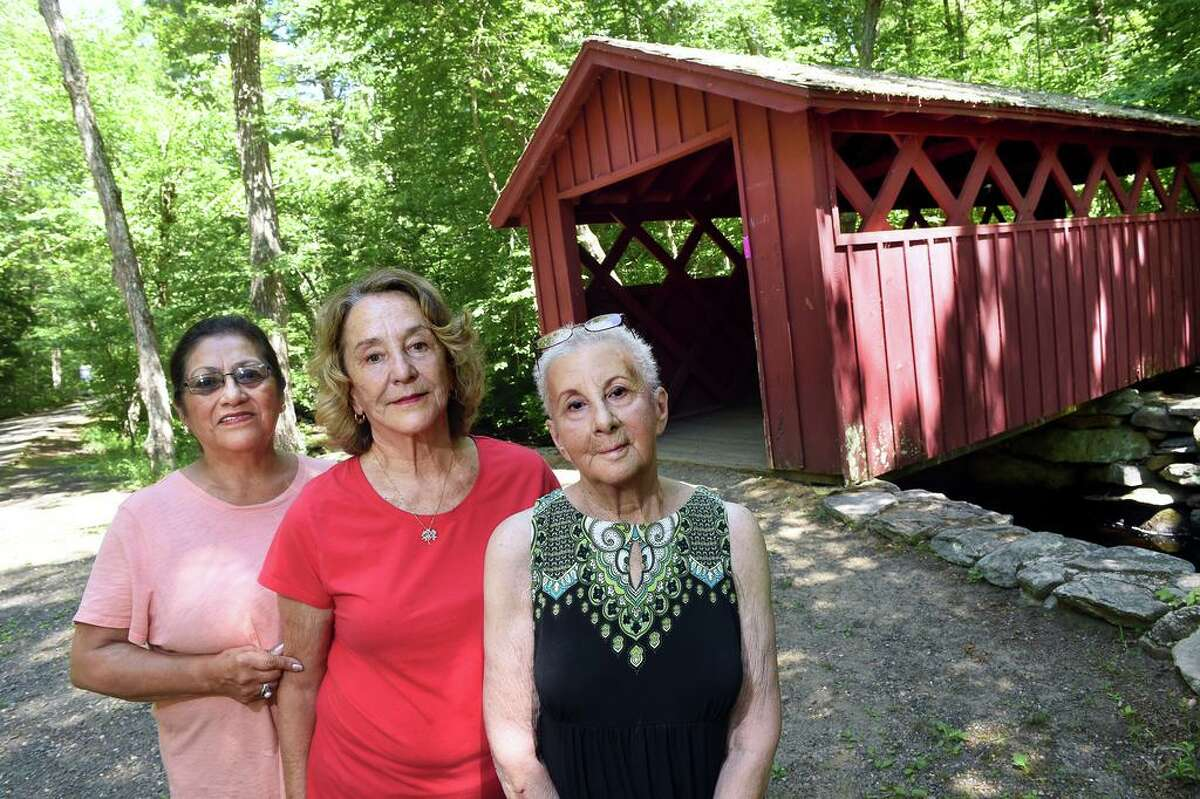 From left, Friends of Chatfield Hollow State Park members Marlene Pesce, Cheryl Buckley and Rhonda Levine are photographed near the covered bridge in the Killingworth park on June 30.