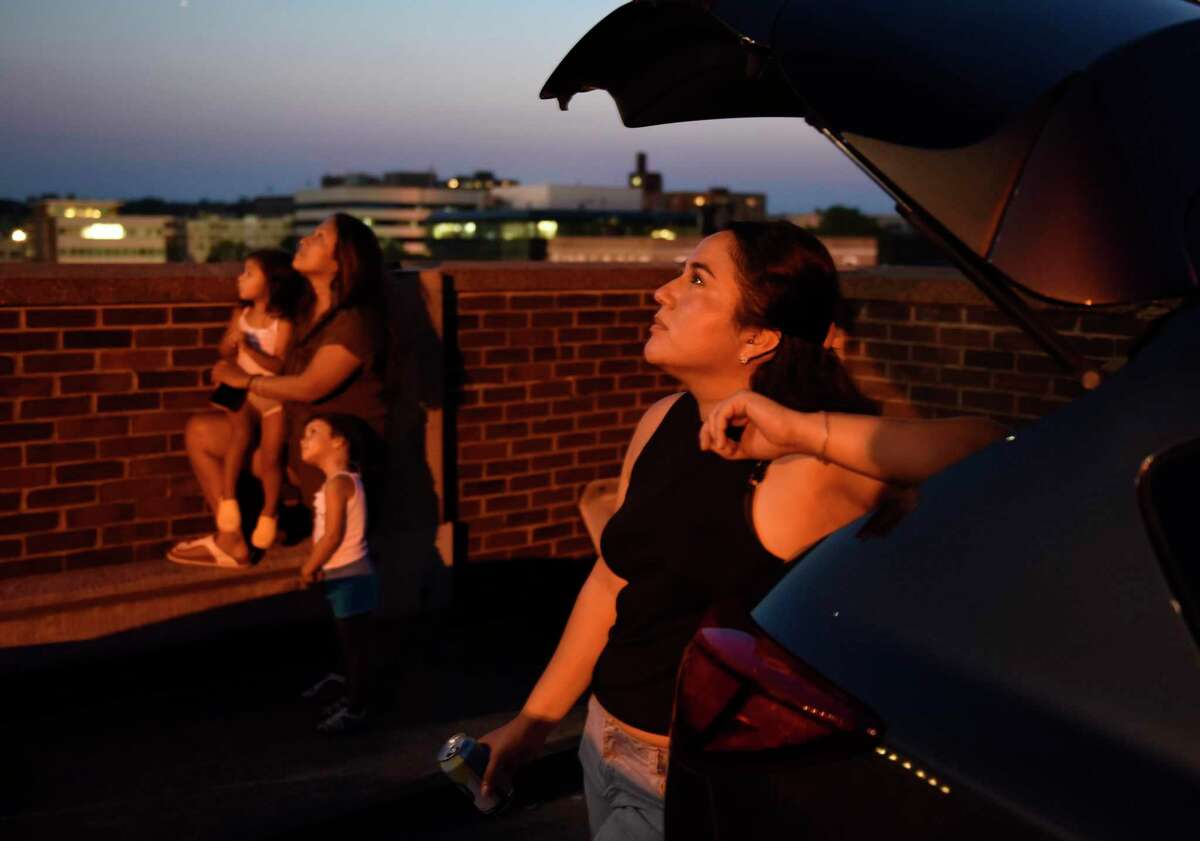 Stamford's Judy Vanejas watches fireworks launched from atop the Landmark Tower in Stamford, Conn. Monday, July 5, 2021. The Fourth of July fireworks show, presented by the Stamford Downtown Special Services District, went on Monday night after being initially postponed due to inclement weather.