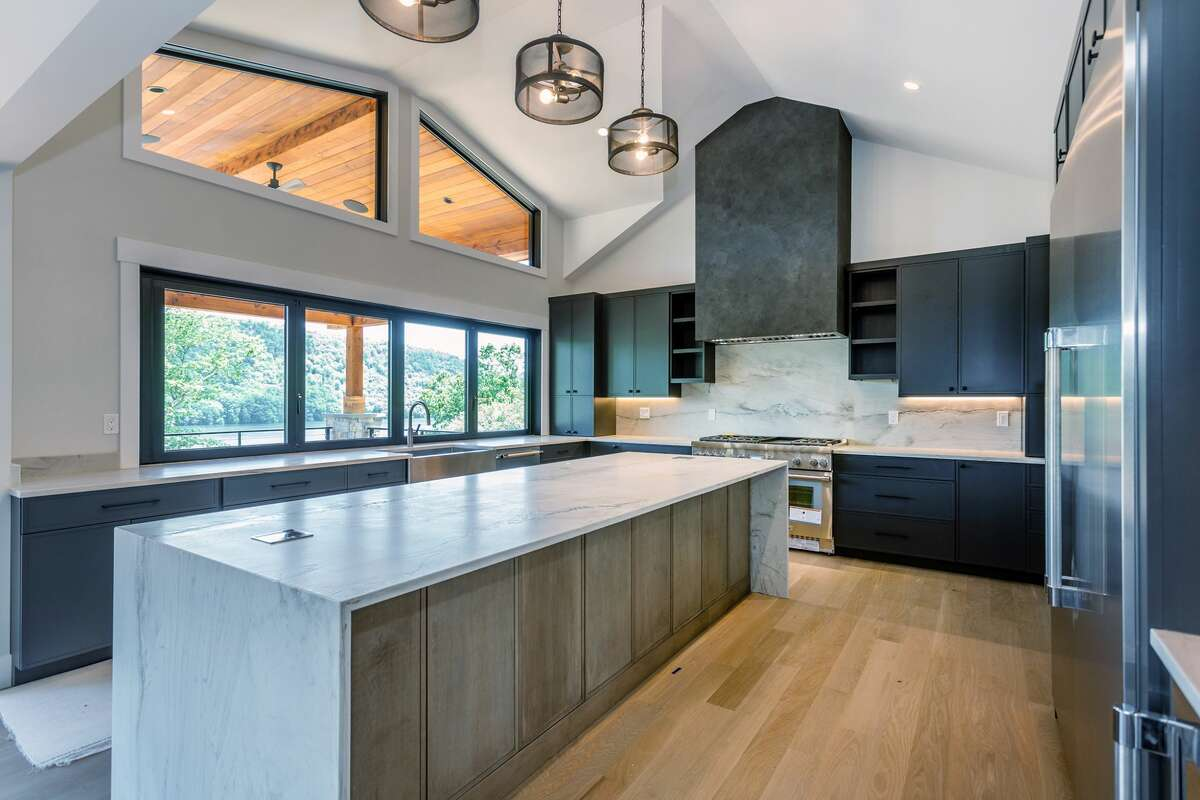 The kitchenhas a 10-foot waterfall island, as well as windows that fully open out to a bar top and covered deck. View listing
