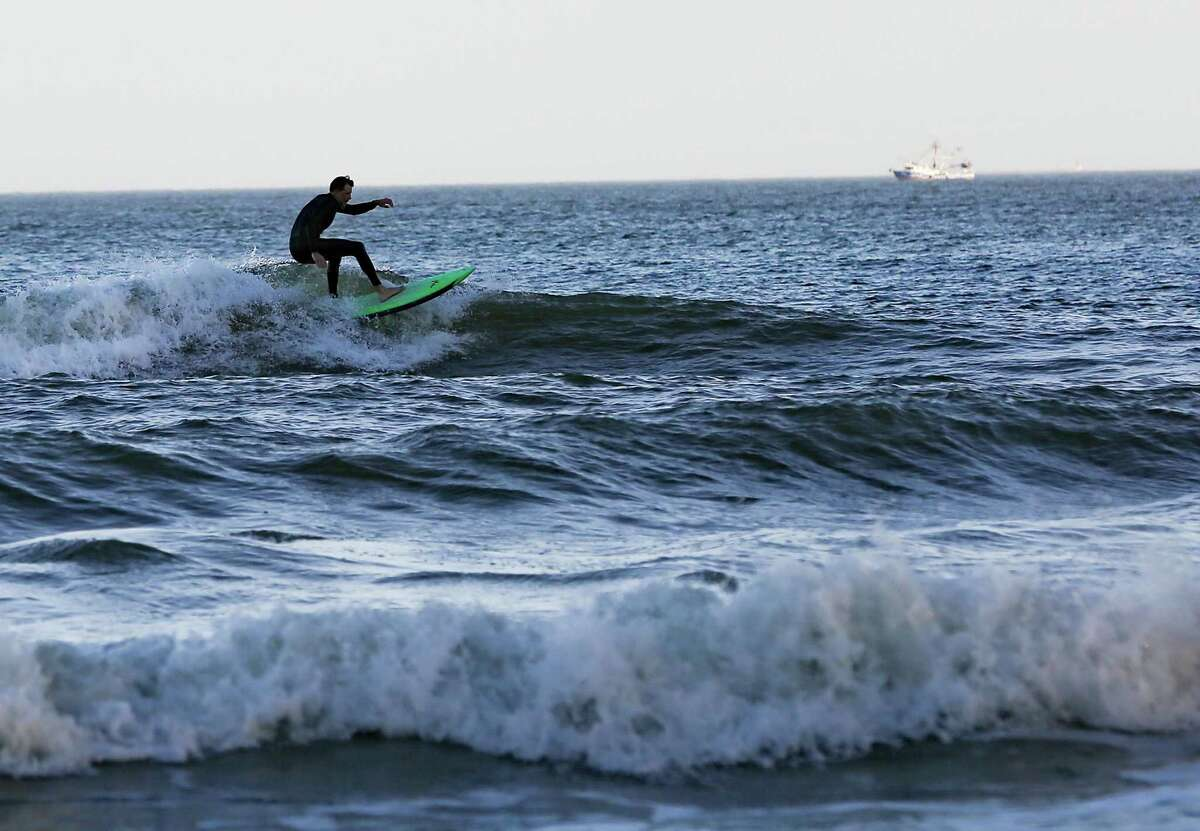A surfer at Galveston Beach during spring break on Wednesday, March 17, 2021.
