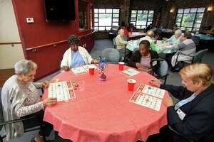Ruby Berry, second from left, plays bingo with her friends at River House Adult Day Center in Greenwich, Conn., on Friday June 25, 2021. A first-of-its-kind report was released Thursday on senior citizens is meant to help communities support healthy aging by addressing nutrition, transportation, housing and more. The report shows racial and economic disparities among seniors in the state. Berry, a Stamford woman, who participates at Greenwich's River House three times per week, has a story that mirrors many others' experiences in the United States.