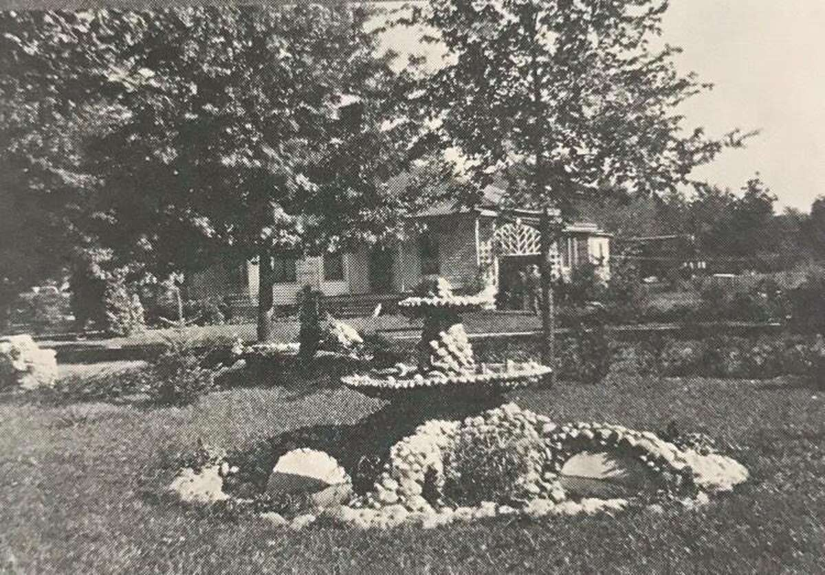 Fountain and pool, grounds of Henry Schultz, with G. Frank Teal home in the background. Schultz was with Thompson Mercantile Co. Teal was a barber. 1926