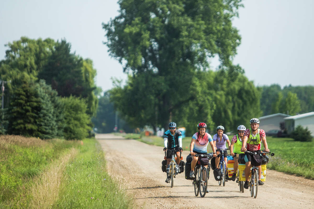 From left, Johnmark Wisniewski, Annie Laurenz, Ellen Laurenz, Claire Laurenz, and Christopher Rasschaert take off on the last leg of a transcontinental cycling trip Monday, July 5, 2021 in Wheeler. (Katy Kildee/kkildee@mdn.net)