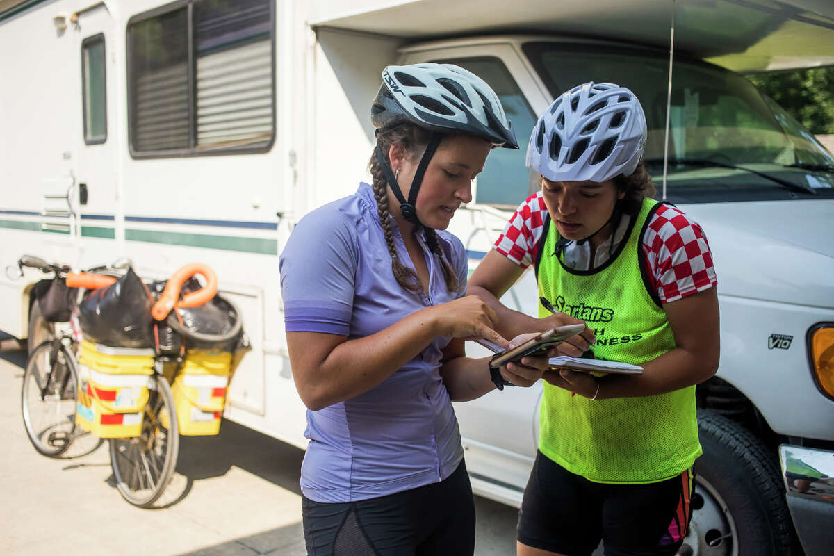 Ellen Laurenz, left, and her sister Claire Laurenz, right, take a look at their route before taking off on the last leg of a transcontinental cycling trip Monday, July 5, 2021 in Wheeler. (Katy Kildee/kkildee@mdn.net)