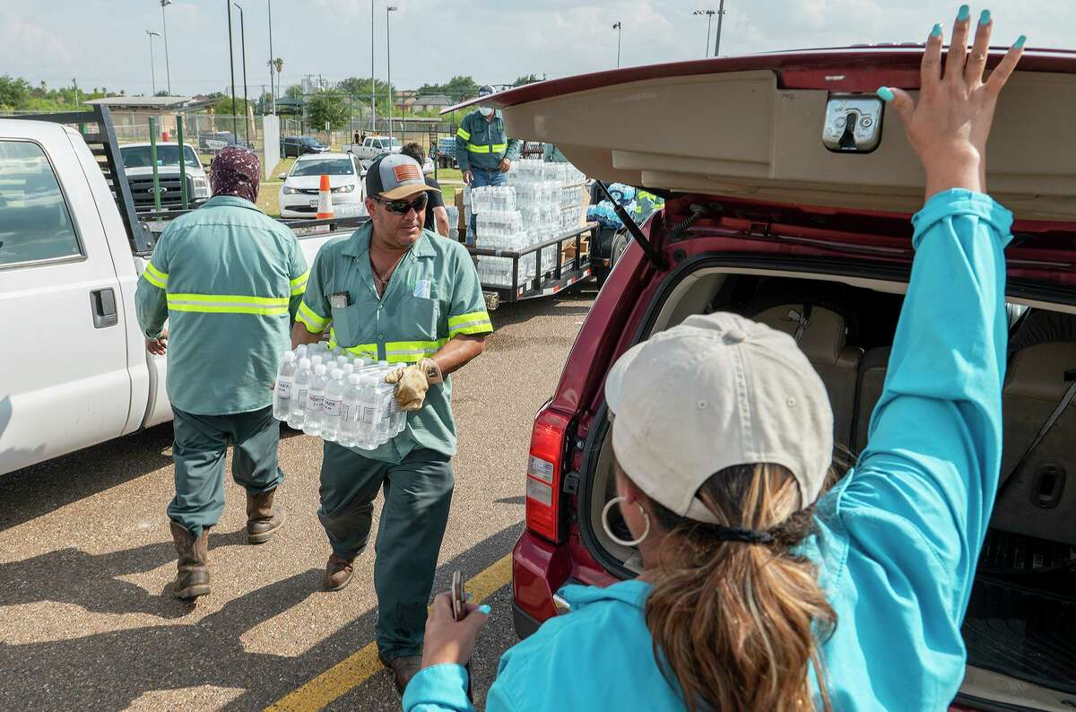 City of Laredo Parks and Recreation crew member Federico Cruz helps load cases of bottled water in response to a boil water notice Monday, July 5, 2021, during a water distribution at Independence Hills Regional Park.