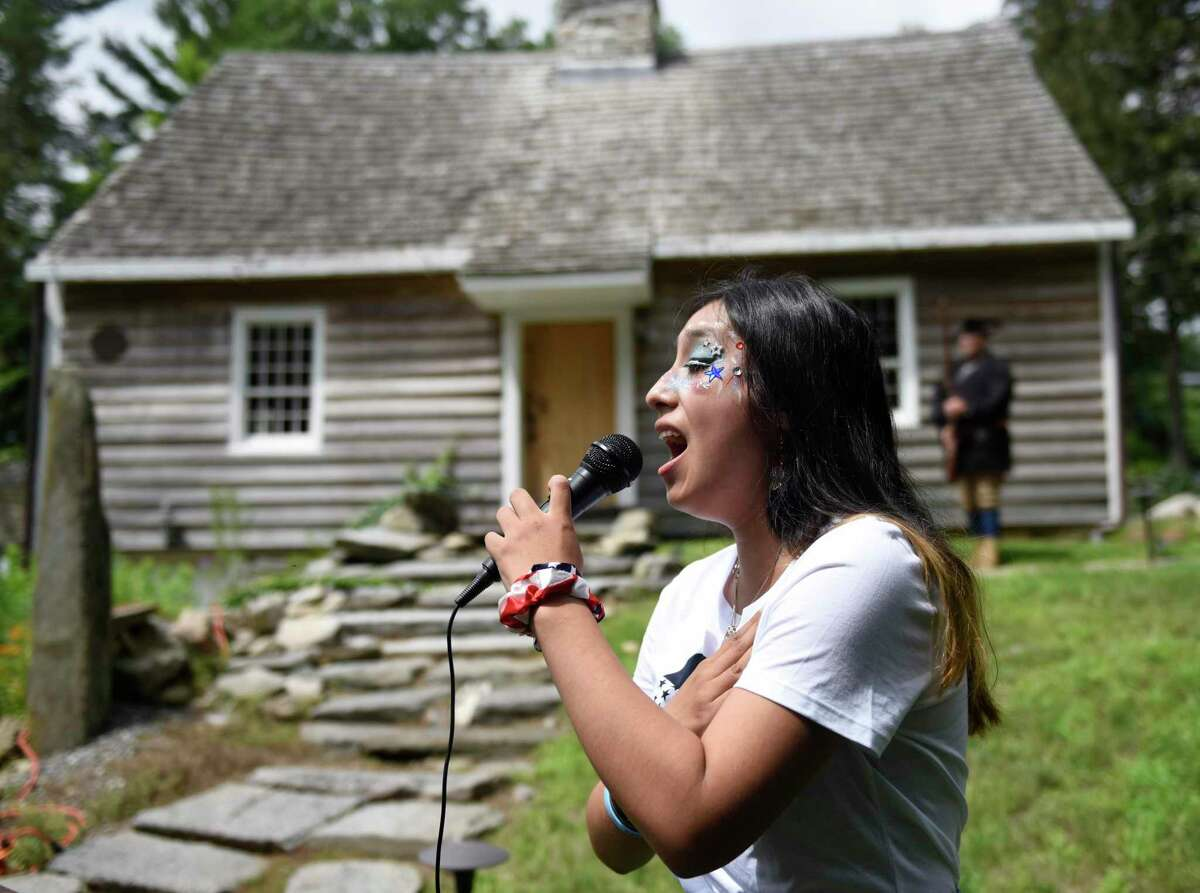 """Victoria Iparraguirre sings """"The Star-Spangled Banner"""" during the third annual Independence Day reading at the Stamford History Center on Sunday. People dressed in character as Isaac Quintard and Elizabeth Cady Stanton read the Declaration of Independence and Declaration of Rights and Sentiments on the steps of the Hoyt-Barnum House, Stamford's oldest dwelling."""