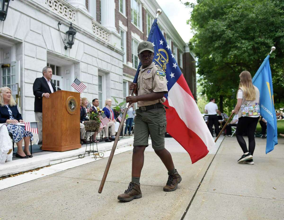 Nathan Hinton, 12, of Boy Scout Troop 35, carries a flag during the Fourth of July Celebration at Town Hall in Greenwich, Conn. Sunday, July 4, 2021. Presented by the Independence Day Association of Greenwich, the ceremony featured a flag raising, patriotic songs, reading of the Declaration of Independence, and honoring of Revolutionary War patriots.