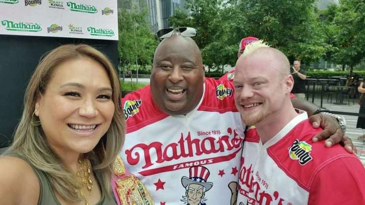 Nicholas Wehry, right a Connecticut native, pictured here with his wife and another competitor, came in third at the annual Nathan's Hot Dog Eating Contest in New York on Sunday, July 4, 2021.