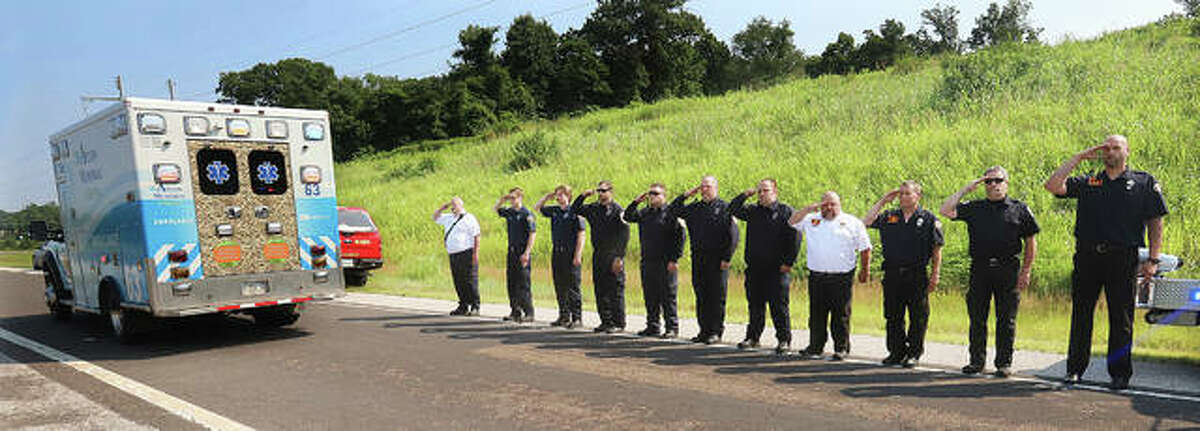 """Firefighters from Rosewood Heights, Meadowbrook and Cottage Hills salute Tuesday from the shoulder of the exit ramp from Illinois Route 255 onto Route 111 as the ambulance carrying South Roxana Fire Chief William """"Todd"""" Werner, passes by. Werner died last week, reportedly from a heart attack."""
