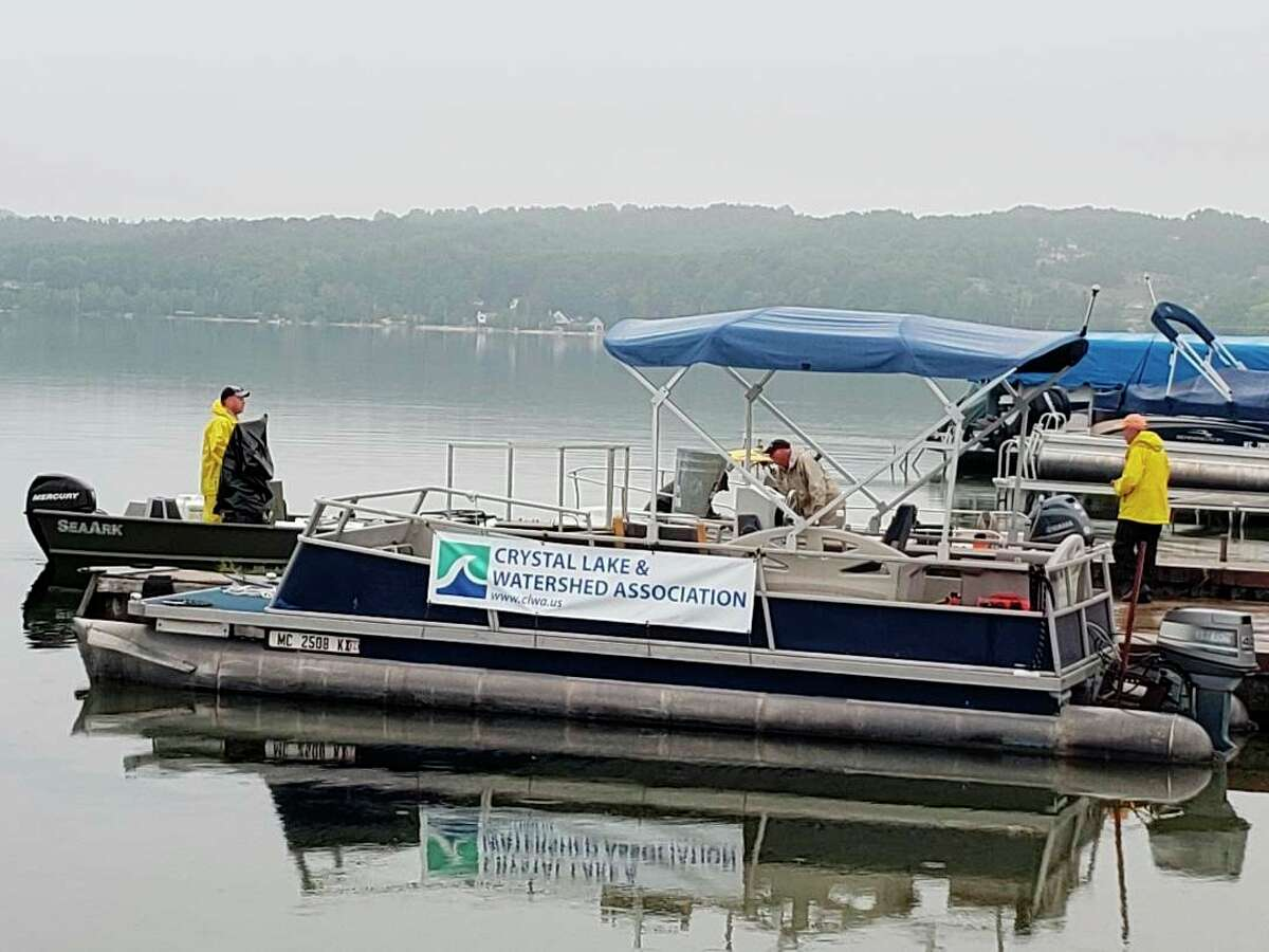 Jim Hamp of the Crystal Lake & Watershed Associationobserving the application of the herbicide to control invasive watermilfoil in Crystal Lake. (Courtesy photo)