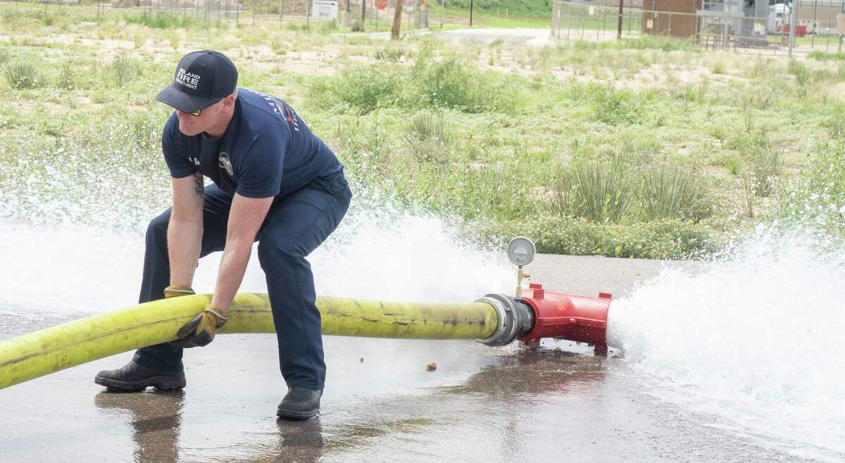 """Midland fire department personel Dyllon Bomer, adjusts the hose as he and other fire department personel check the water flow of a hydrant off Bluebird Lane 07/06/2021 as they flush the water system as City of Midland switches from """"Chloramine, a combination of chlorine and ammonia, is normally used as a disinfectant to remove possible bacteria and viruses from water supplies in Midland and many other cities across the nation. During a period of approximately 30 days, the City will use only chlorine to disinfect the water supply. """"Free"""" chlorine is a more powerful disinfectant, and this temporary change in the water treatment process denies bacteria the ability to form resistances to the usual disinfection treatment process,"""" from City of Midland web site. Tim Fischer/Reporter-Telegram"""