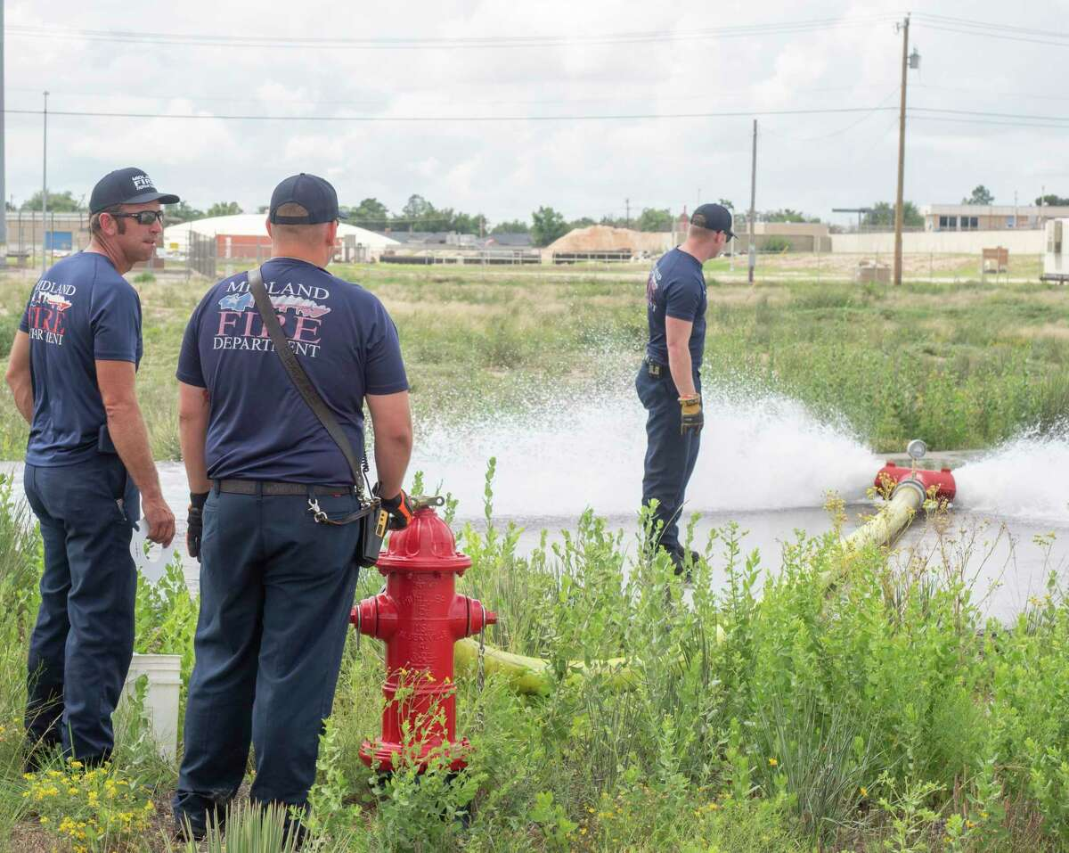 """Midland fire department personel, Mitchell Heater, on hydrant, Dustin Layman and Dyllon Bomer, at the hose, check the water flow of a hydrant off Bluebird Lane 07/06/2021 as they flush the water system as City of Midland switches from """"Chloramine, a combination of chlorine and ammonia, is normally used as a disinfectant to remove possible bacteria and viruses from water supplies in Midland and many other cities across the nation. During a period of approximately 30 days, the City will use only chlorine to disinfect the water supply. """"Free"""" chlorine is a more powerful disinfectant, and this temporary change in the water treatment process denies bacteria the ability to form resistances to the usual disinfection treatment process,"""" from City of Midland web site. Tim Fischer/Reporter-Telegram"""