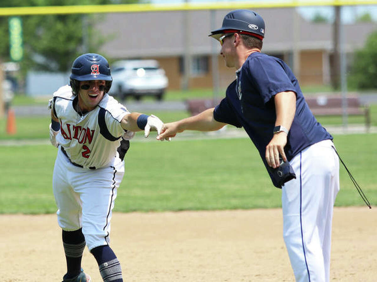 Alton Legion's Cameron Hailstone (left) delivers some gear and gets a fist bump from first base coach Cullen McBride on Sunday after Hailstone's double against Highland in the title game of the Firecracker Classic tournament at Moody Park in Fairview Heights.