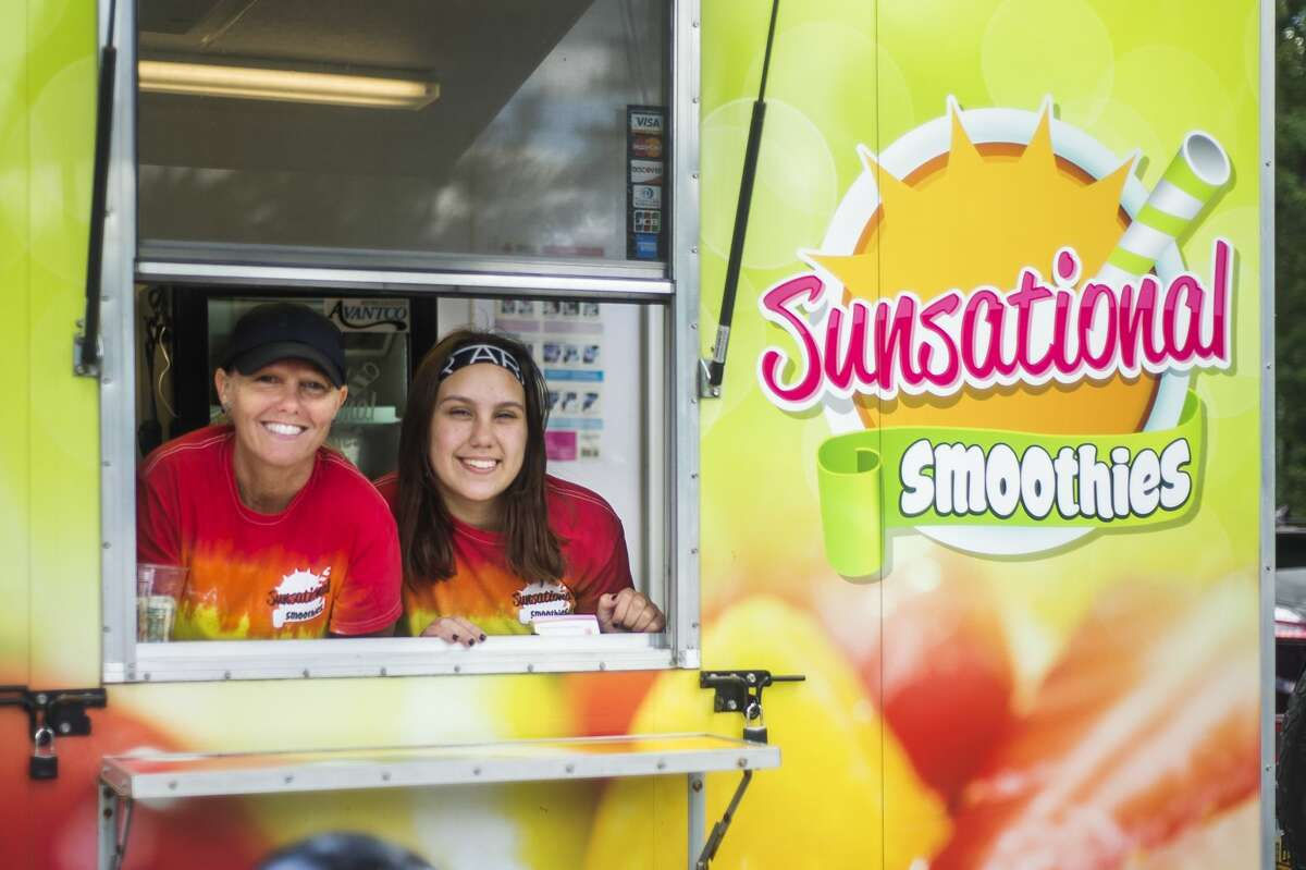 Brandi DesMarteaux, left, and her daughter Maleah, right, pose for a portrait inside the Sunsational Smoothies truck Friday, July 2, 2o21 in Midland. (Katy Kildee/kkildee@mdn.net)