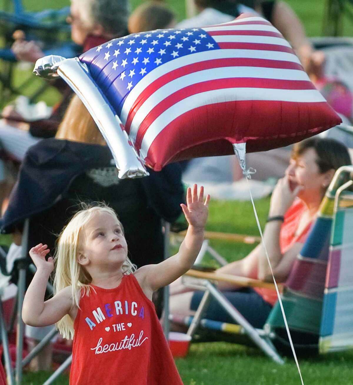 Violet Nosenzo, 3, of Ridgefield, bats around a balloon at the town's annual fireworks display, which kicked off at Ridgefield High School's Tiger Hollow Stadium on July 5.