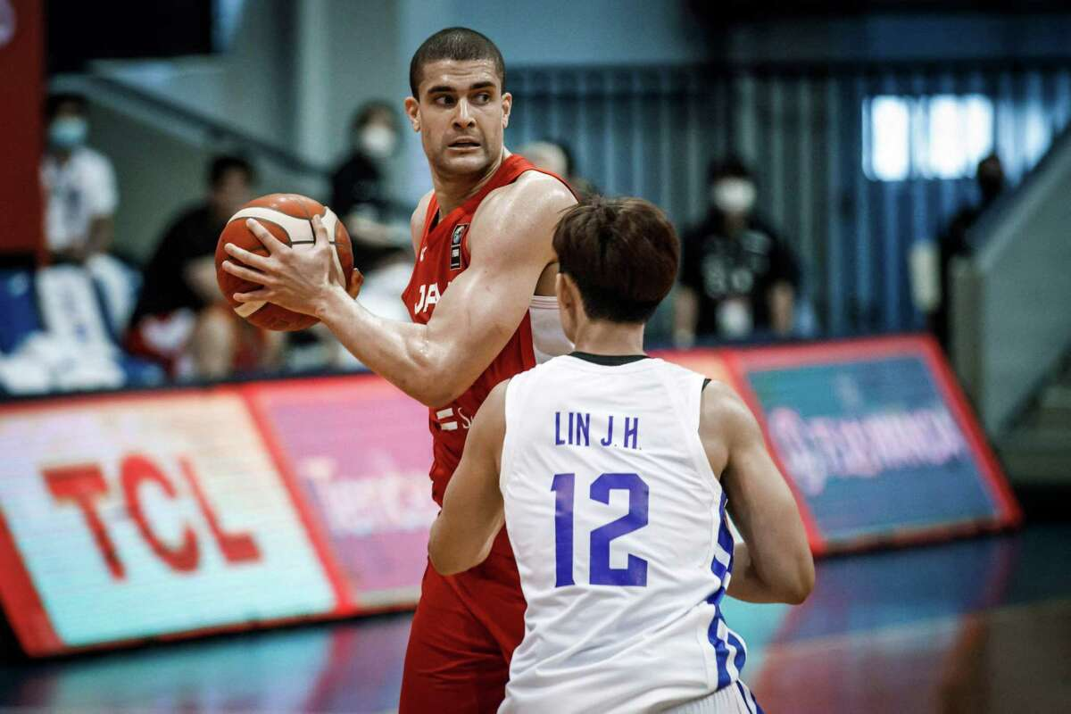 """This handout photo taken on June 18, 2021 and received from the FIBA Asia Cup shows Japan's Gavin Edwards (L) looking to pass the ball in front of Taiwan's Lin Jen-hung during the FIBA Asia Cup basketball qualifier match between Japan and Taiwan in Angeles City, north of Manila. (Photo by Paul Ryan TAN / FIBA Asia Cup / AFP) / -----EDITORS NOTE --- RESTRICTED TO EDITORIAL USE - MANDATORY CREDIT """"AFP PHOTO / PAUL RYAN TAN/ FIBA Asia Cup"""" - NO MARKETING - NO ADVERTISING CAMPAIGNS - DISTRIBUTED AS A SERVICE TO CLIENTS (Photo by PAUL RYAN TAN/FIBA Asia Cup/AFP via Getty Images)"""
